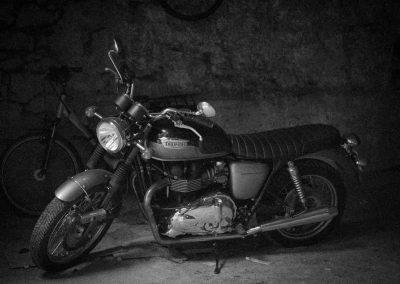Moto Triumph Bonneville en noir et blanc dans une remise du vieille Annecy