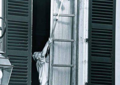 Une personne âgée nettoie sa fenêtre