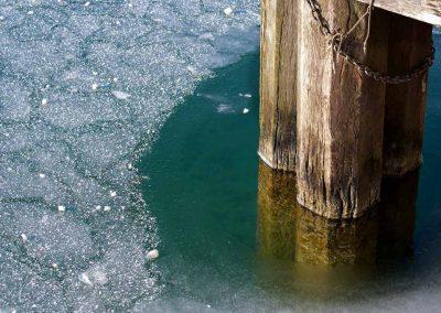Glace autour d'un pied de ponton gelé sur le canal à Annecy